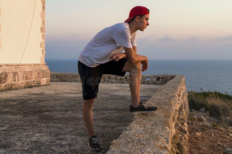 Jonge mens, die de zonsondergang bekijken stock foto