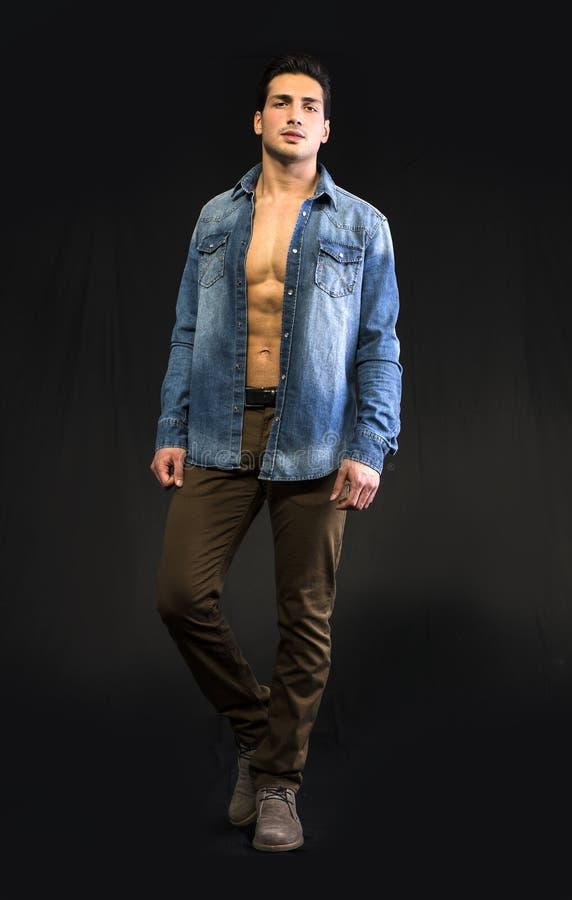 Jonge mens die denimoverhemd open op naakte borst dragen royalty-vrije stock foto