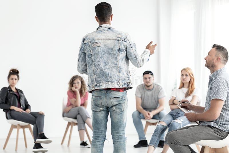 Jonge mens die in denimuitrusting aan een groep tieners spreken met royalty-vrije stock foto
