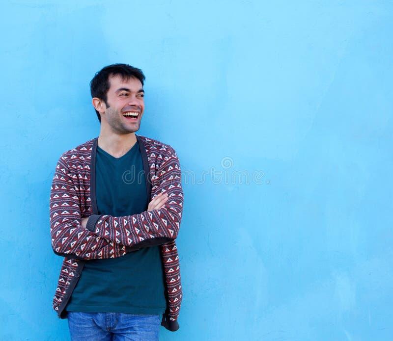 Jonge mens die die met wapens glimlachen op blauwe achtergrond worden gekruist stock foto