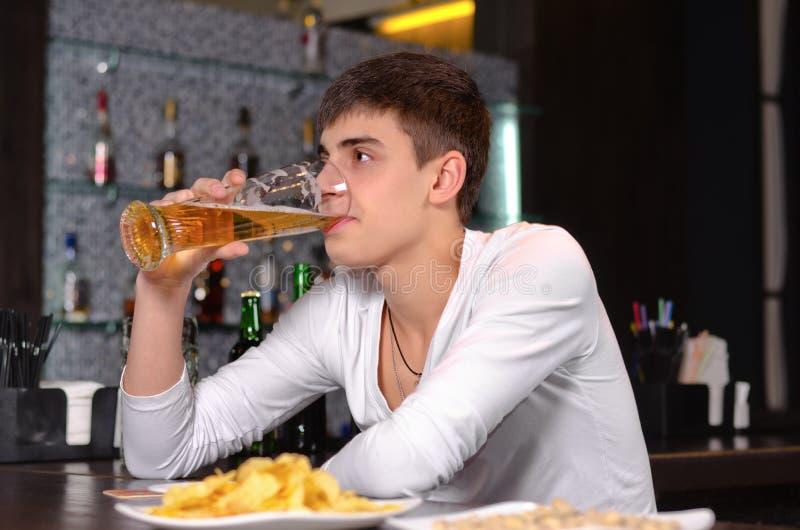 Jonge mens die drinkend een bier in de bar geniet van stock afbeelding