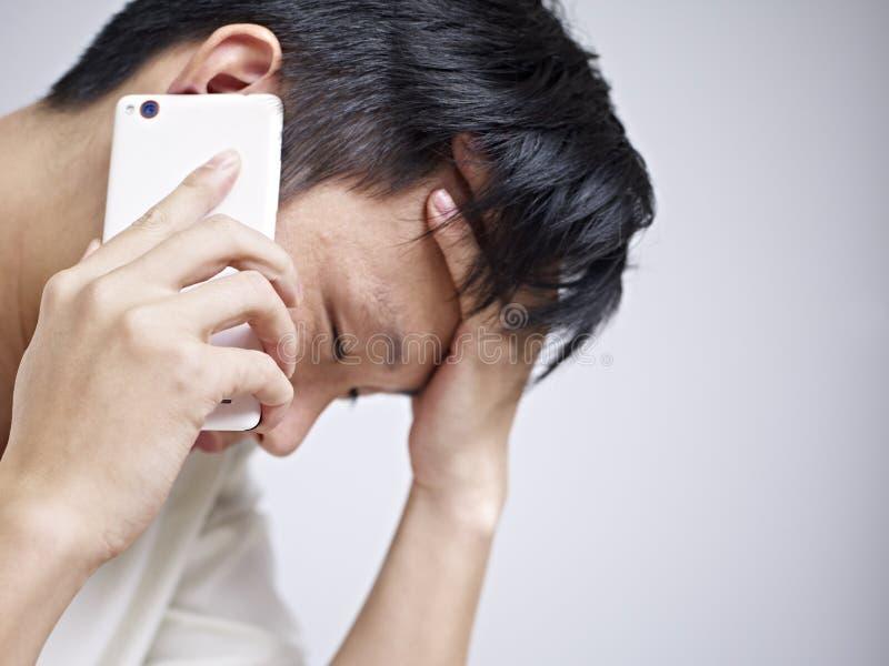 Jonge mens die droevig en gedeprimeerd kijken stock afbeelding