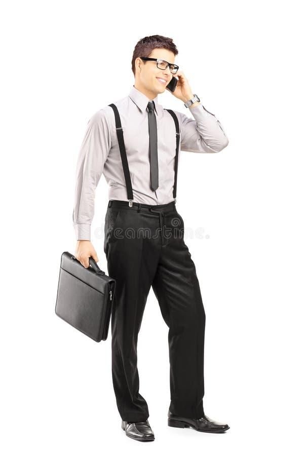 Jonge mens die een aktentas houden en op een telefoon spreken stock afbeelding