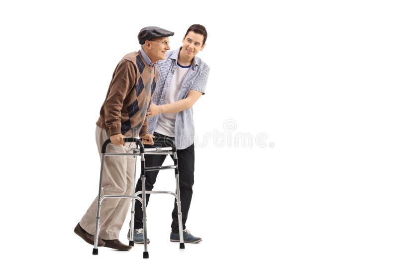 Jonge mens die een bejaarde met een leurder helpen stock foto's