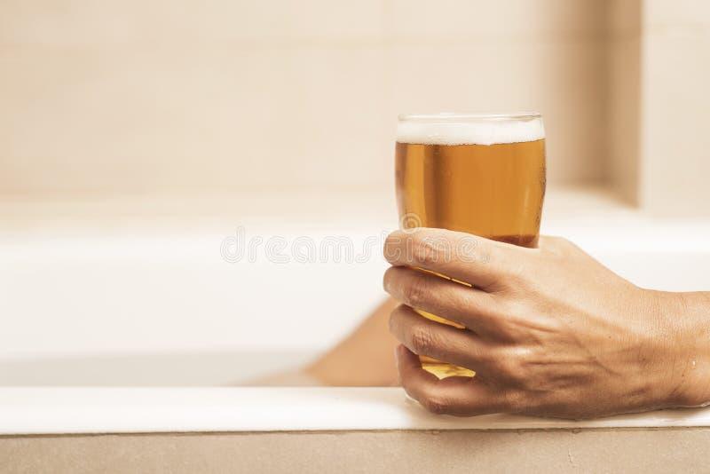 Jonge mens die een bier op de badkuip drinken stock fotografie