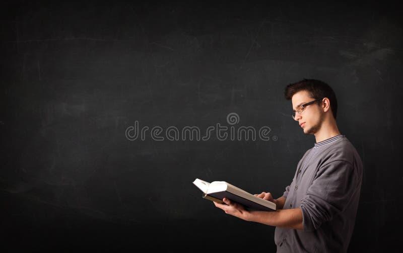 Jonge mens die een boek lezen stock foto's