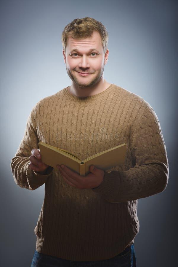 Jonge mens die een boek lezen en op grijze achtergrond glimlachen stock fotografie