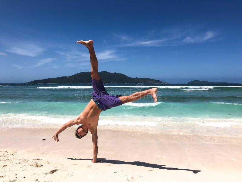 Jonge mens die een cartwheel doen bij een tropisch strand in Seychellen royalty-vrije stock fotografie