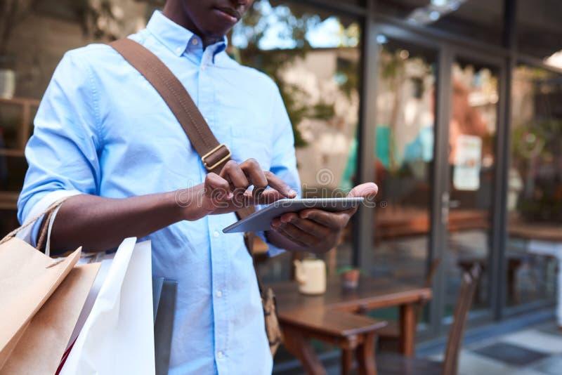 Jonge mens die een digitale tablet gebruiken terwijl uit het winkelen royalty-vrije stock foto