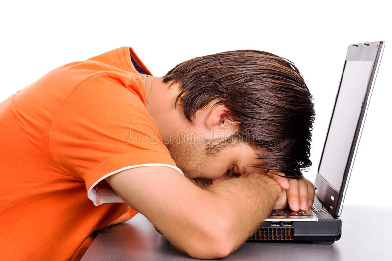 Jonge mens die een dutje op zijn laptop nemen royalty-vrije stock afbeeldingen