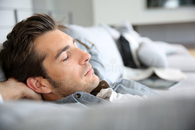 Jonge mens die een dutje thuis nemen royalty-vrije stock afbeeldingen