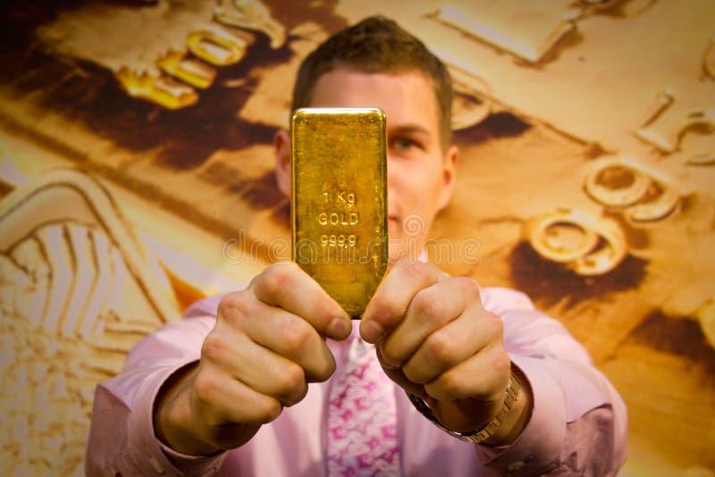 Jonge mens die een gouden bar houden stock foto's