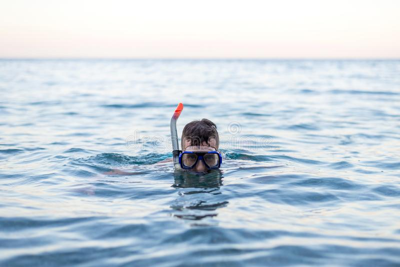 Jonge mens die in een het duiken masker zwemmen royalty-vrije stock foto