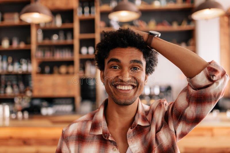 Jonge mens die in een koffie met hand op hoofd glimlachen royalty-vrije stock foto