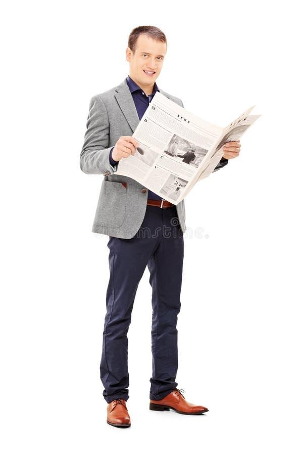 Jonge mens die een krant houden stock foto's