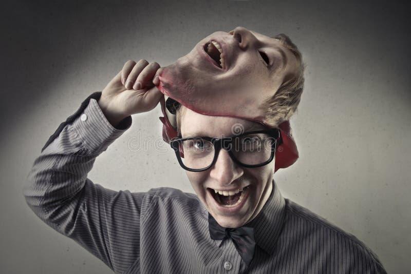 Jonge mens die een masker opstijgt stock foto