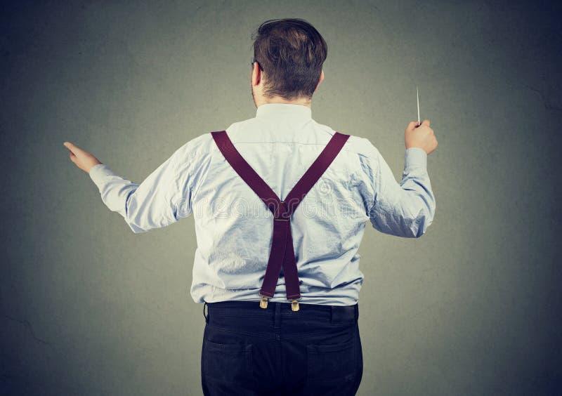 Jonge mens die een orkest leiden stock afbeelding