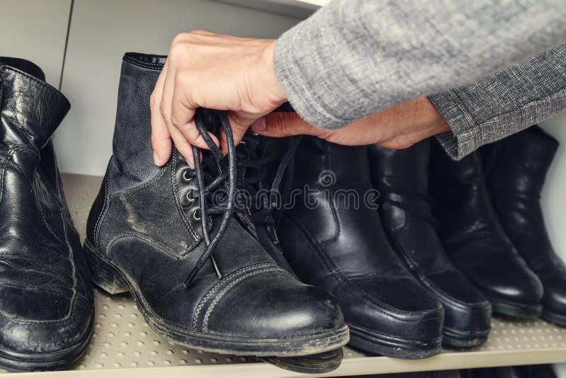 Jonge mens die een paar laarzen van de kast plukken royalty-vrije stock fotografie