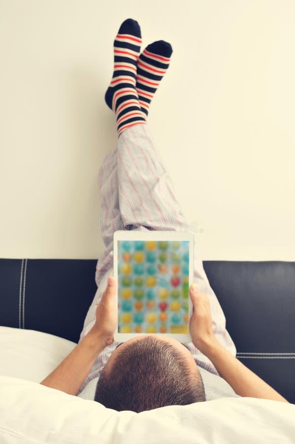 Jonge mens die een tablet in bed gebruiken royalty-vrije stock foto's