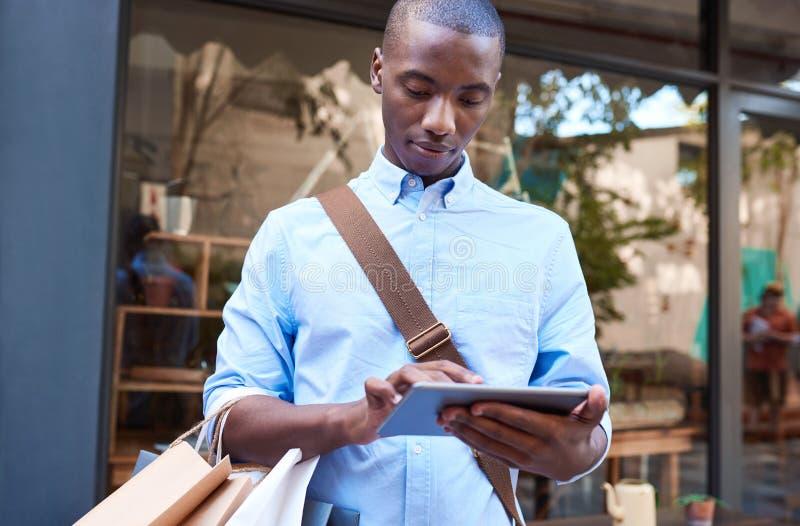 Jonge mens die een tablet gebruiken terwijl het winkelen in de stad stock foto