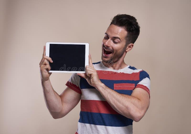 Jonge mens die een tablet in studioschot tonen stock afbeelding