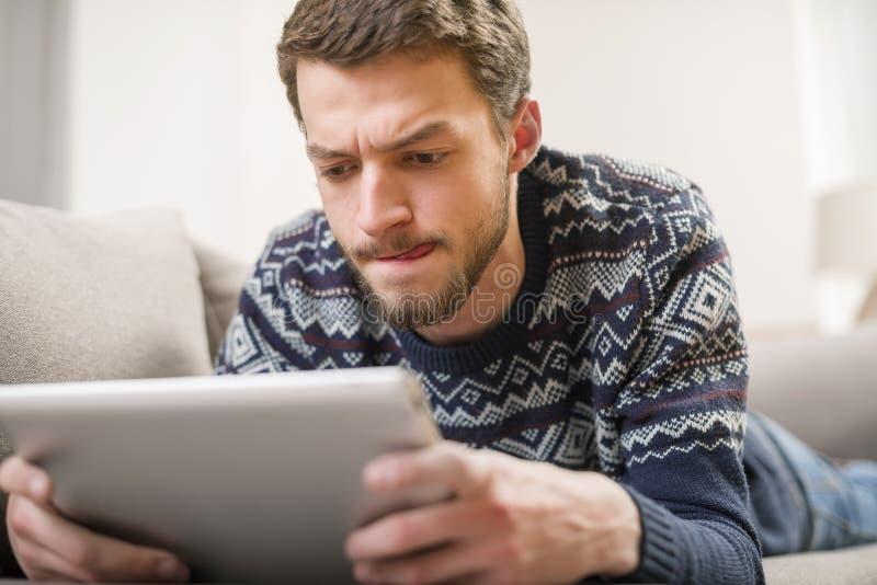 Jonge mens die een tabletcomputer bekijken terwijl het liggen op de laag royalty-vrije stock fotografie