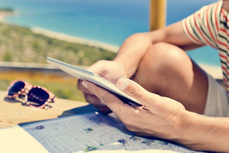Jonge mens die een tabletcomputer in openlucht met behulp van stock fotografie