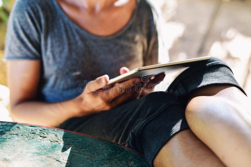 Jonge mens die een tabletcomputer in openlucht met behulp van royalty-vrije stock fotografie