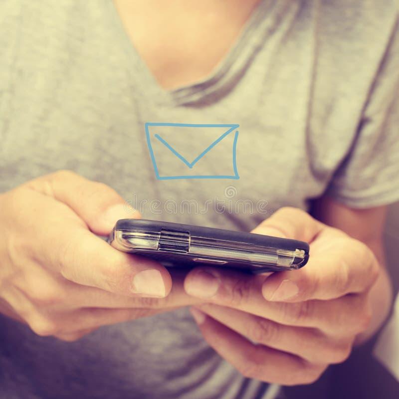 Jonge mens die of een tekstbericht verzenden ontvangen stock foto's