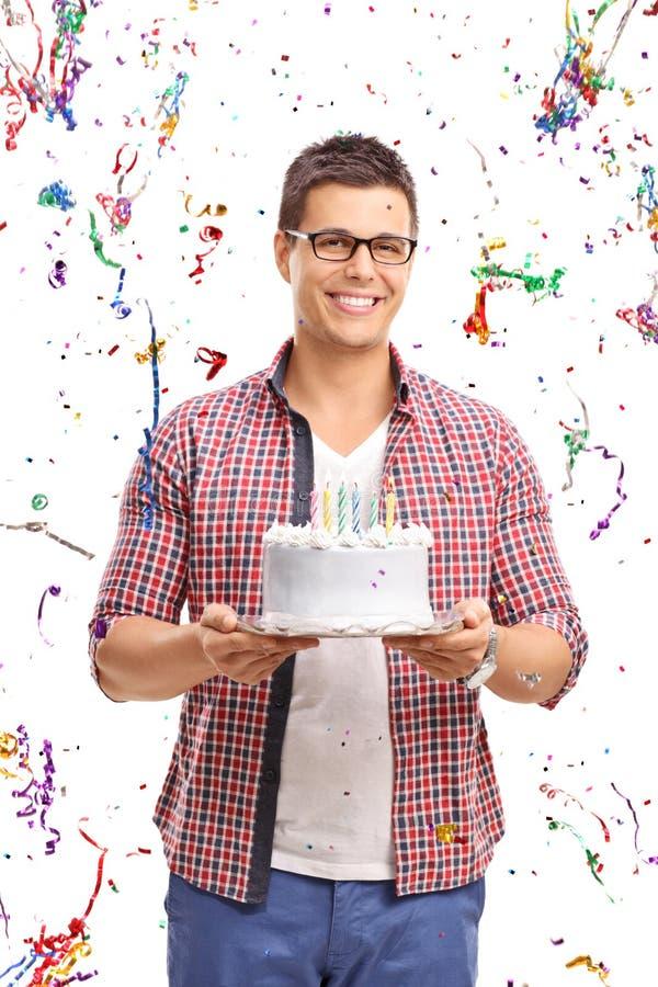 Jonge mens die een verjaardagscake dragen stock foto