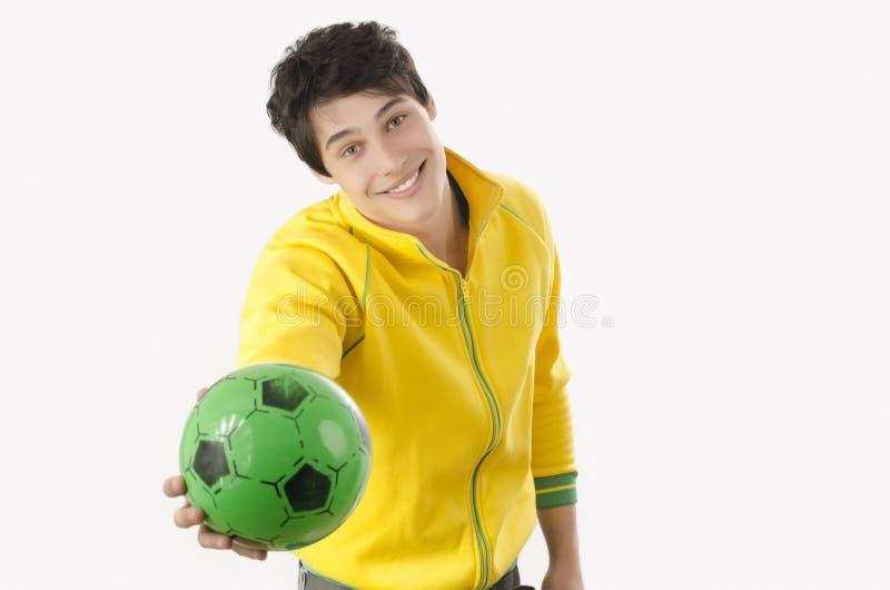 Jonge mens die een voetbalbal aanbieden stock afbeelding