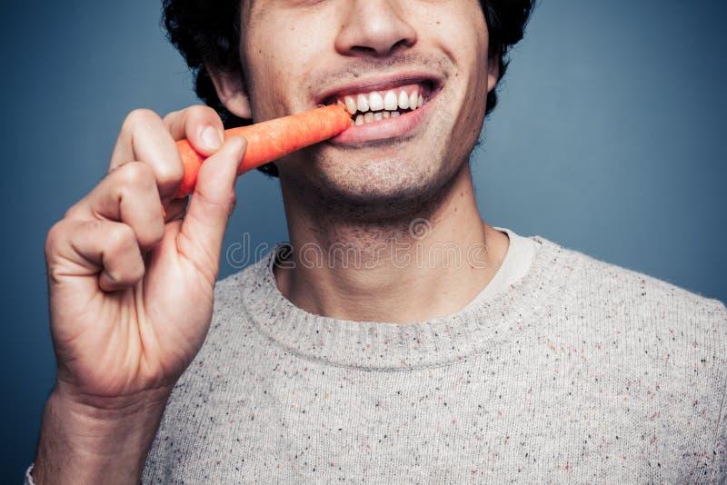 Jonge mens die een wortel eten royalty-vrije stock afbeeldingen