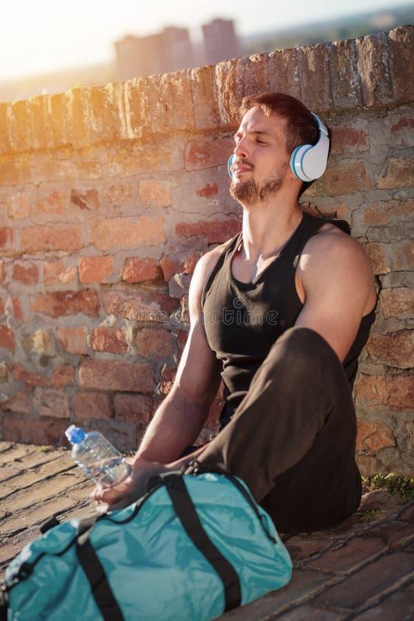 Jonge mens die en aan muziek na een harde training ontspannen luisteren stock fotografie