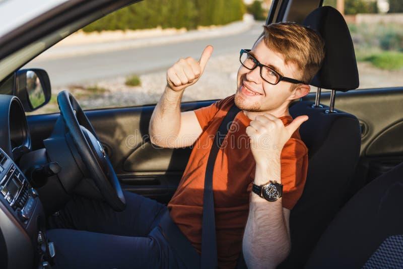 Jonge mens die en duimen in zijn auto glimlachen tonen royalty-vrije stock foto