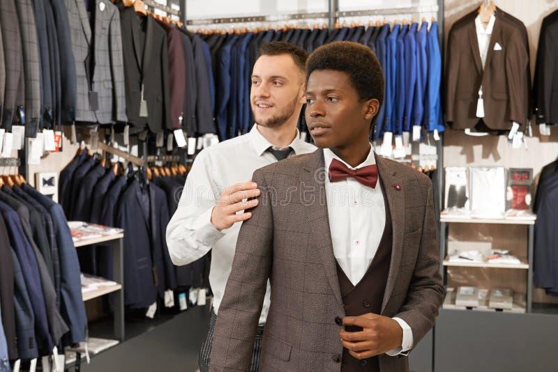 Jonge mens die en kostuum in winkel proberen kiezen stock foto's