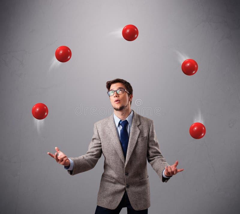 Jonge mens die en zich met rode ballen bevinden jongleren met royalty-vrije stock fotografie