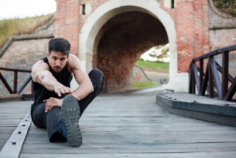 Jonge mens die en zich na de training uitrekken ontspannen royalty-vrije stock afbeelding
