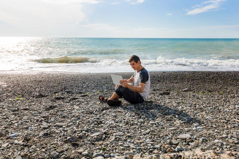 Jonge mens die freelancer aan het strand werken stock afbeeldingen