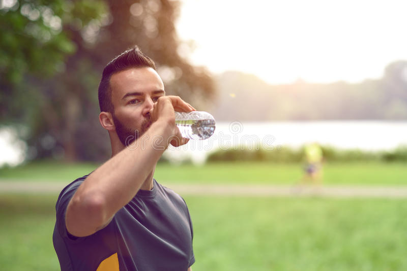 Jonge mens die gebotteld water drinkt stock fotografie