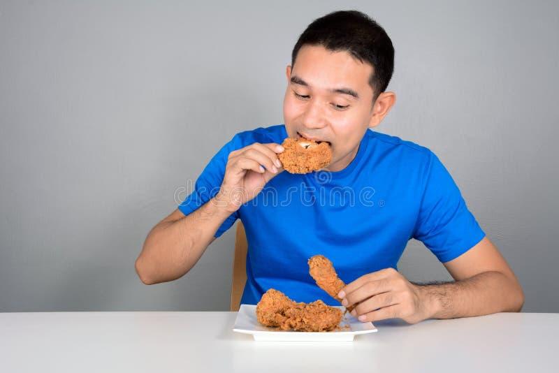 Jonge mens die gebraden kip bijten stock afbeeldingen