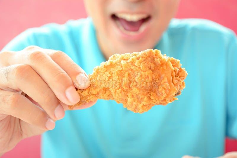 Jonge mens die gefrituurde kippenbeen of trommelstok eten royalty-vrije stock foto