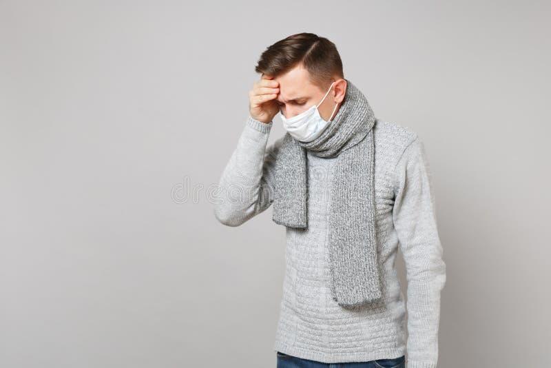 Jonge mens die in die grijze sweater, masker van het sjaal het steriele gezicht met verminderd hoofd handen op voorhoofd zetten o royalty-vrije stock fotografie