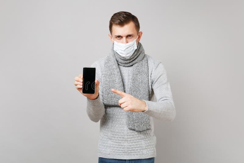 Jonge mens die in grijze sweater, masker van het sjaal het steriele gezicht wijsvinger op mobiele telefoon met het lege lege sche royalty-vrije stock afbeeldingen