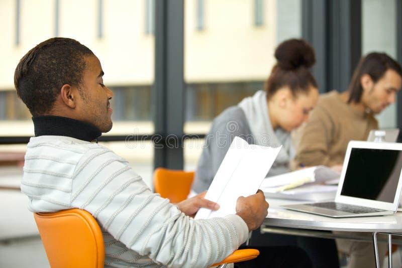 Jonge mens die hard voor examens bestuderen royalty-vrije stock afbeeldingen
