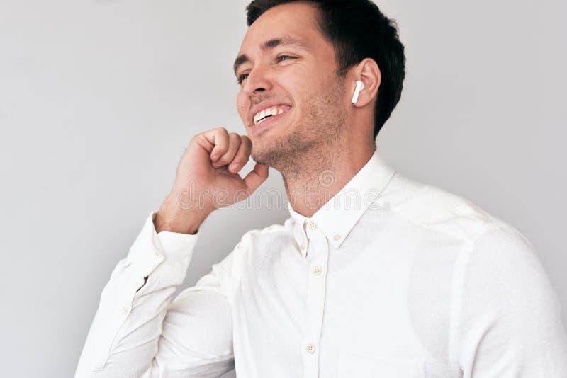 Jonge mens die, hebbend een vraag via draadloze die oortelefoons met een collega glimlachen op witte muur wordt geïsoleerd stock foto