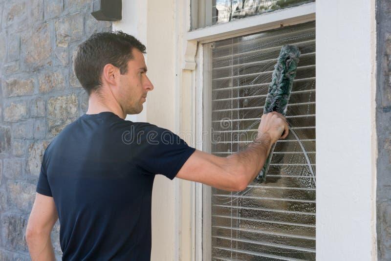 Jonge mens die het buitenvenster van een huis wassen royalty-vrije stock foto