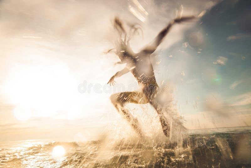 Jonge Mens die in het Overzees springen stock foto's
