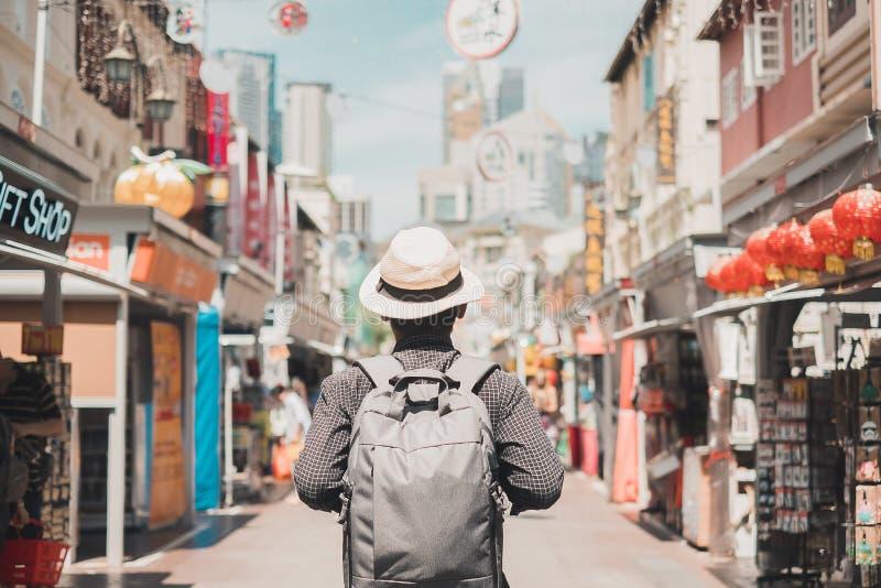 Jonge mens die hipster met rugzak en hoed, gelukkige solo reiziger reizen die bij de markt van de Chinatownstraat in Singapore lo stock afbeeldingen