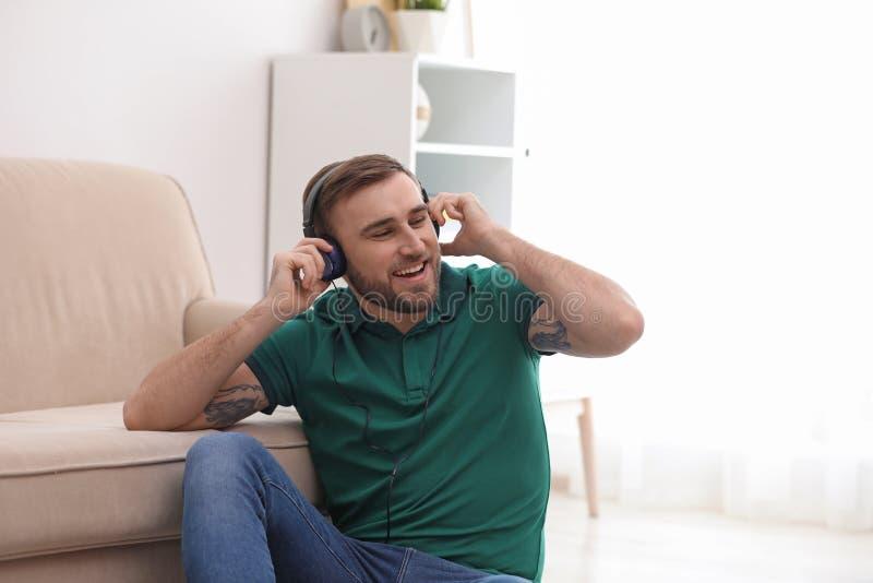 Jonge mens die in hoofdtelefoons van muziek genieten royalty-vrije stock afbeelding