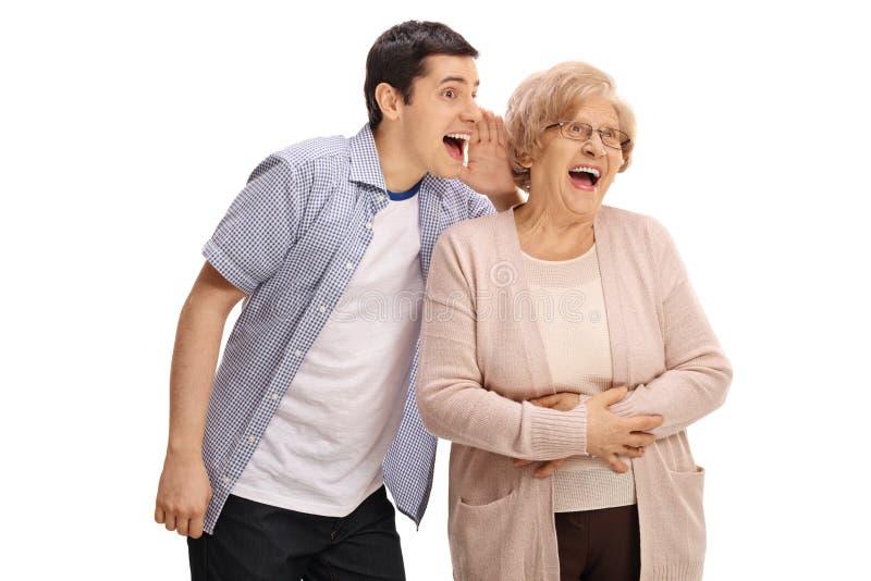 Jonge mens die iets fluisteren grappig aan een bejaarde dame stock afbeeldingen